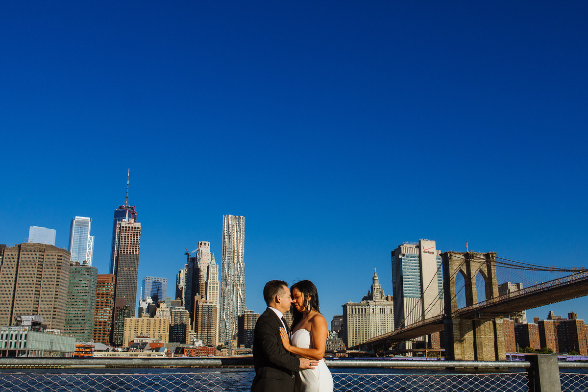 Couple standing in front of Manhattan skyline and Brooklyn bridge to the side.