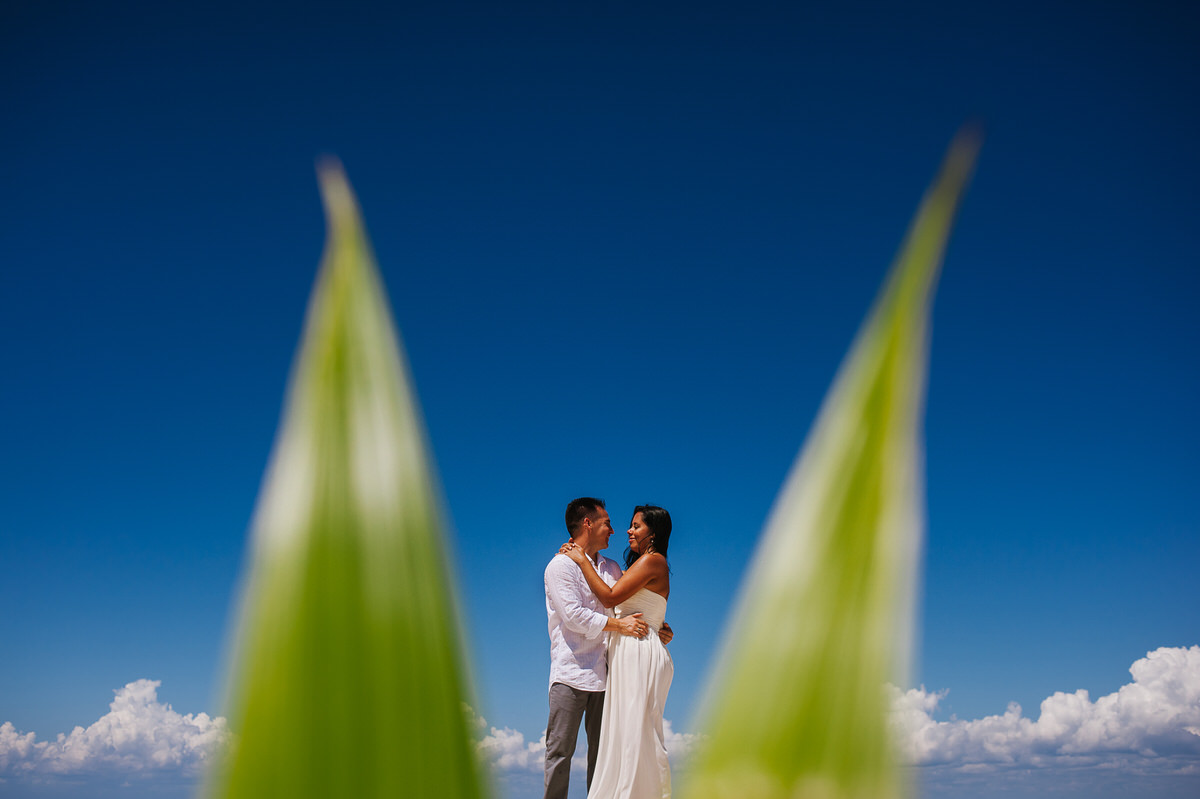 Cozumel Session blue sky and green leaves framing couple