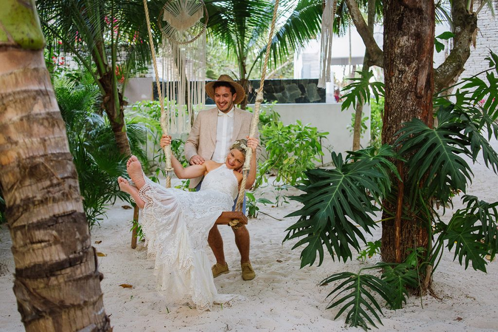 Bride and groom in Tulum on a swing. Boho couple.