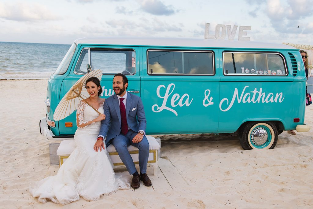 vintage van on the beach with Bride and groom sitting in front of it holding an umbrella in Playa del Secreto.