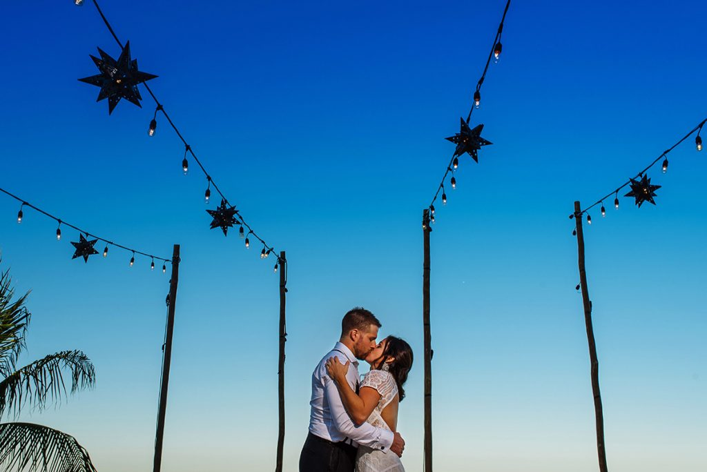 Bride and groom at The Finest kissing during sunset, blue hour with beautiful blue sky and framed by wooden poles and mexican metal stars.