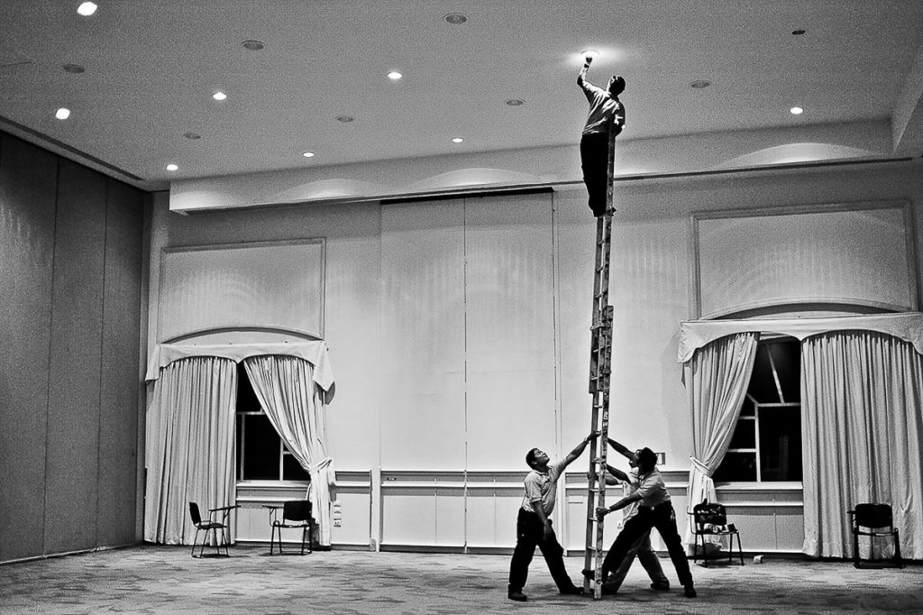 Four employees at an all-inclusive Cancun resort changing a light bulb holding a ladder. Black and white photo.