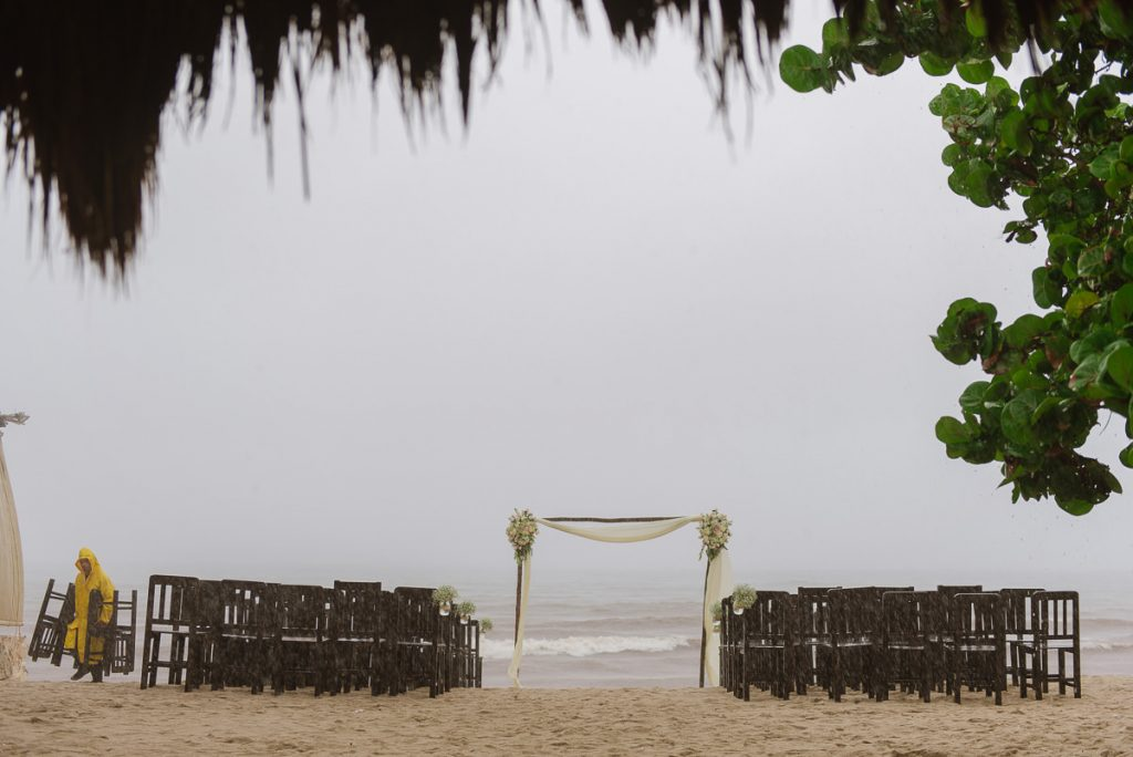 Wedding venue employee moving beach ceremony chairs during heavy rain.