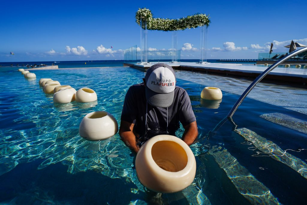 Planner1 employee in pool arranging floating candles for beach ceremony decor in Cancun.