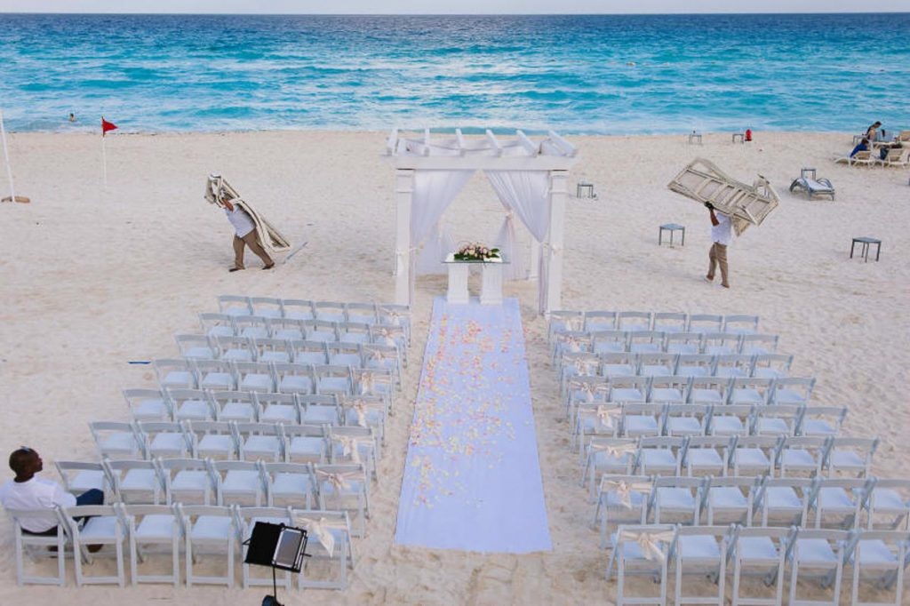 Hotel employees moving loungers from the beach to prepare the wedding ceremony location in Cancun.