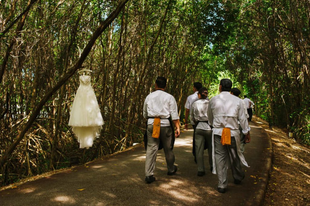 Group of cooks  and chefs looking at a wedding gown hanging from a tree in the middle of a jungle path in Cancun, Mexico.