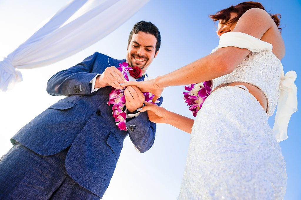 Groom puts ring on brides finger, low angled against blue sky in outdoors wedding in Tres Ríos