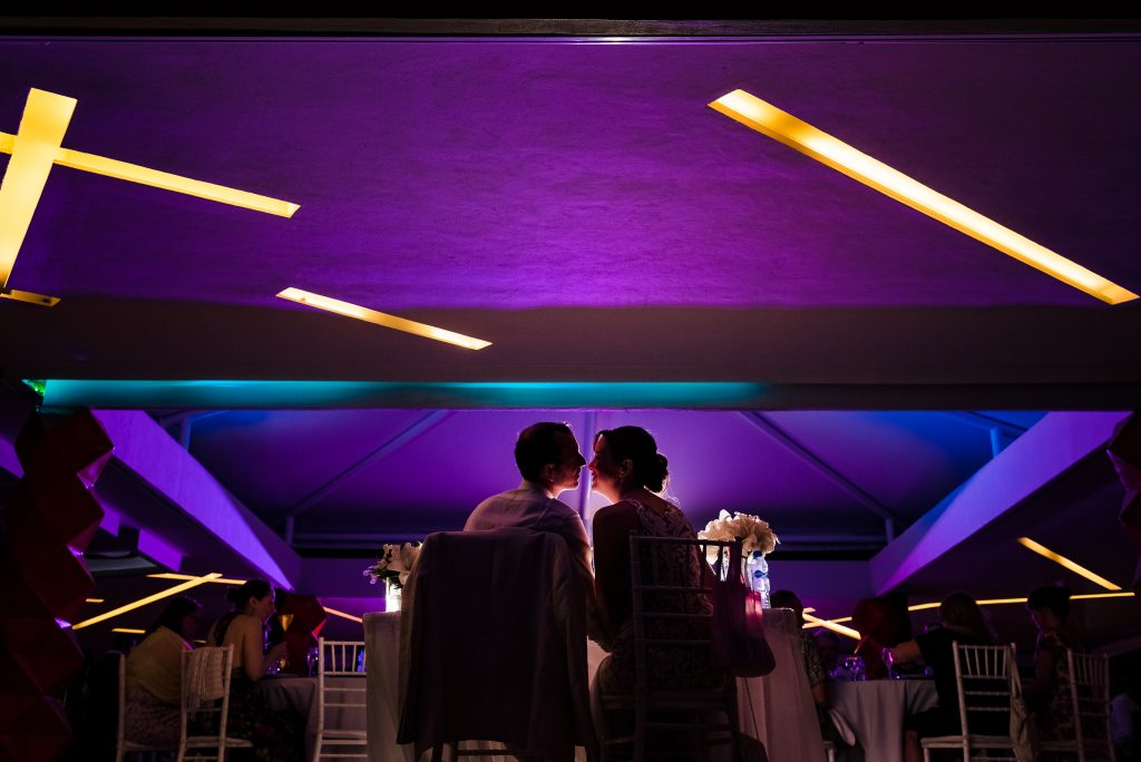 Backlit wedding reception portrait of bride and groom at their table with colorful led lit walls